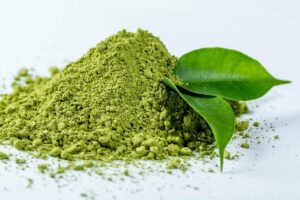 close up photo of heap of matcha powder with green tea leaves on white background