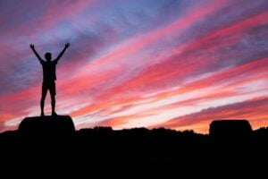 Silhoutte of man standing on a high ground under red and blue skies